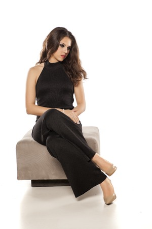 young elegant woman in trousers sitting on the ottoman Archivio Fotografico