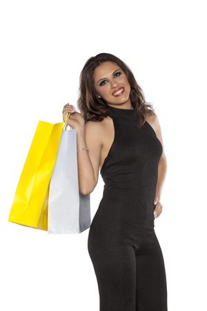 A woman in one-piece dress, trousers and blouses, holding a shopping bags Stock Photo