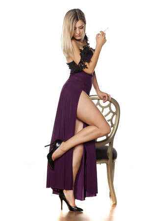 jovem bonita posando com uma cadeira em um vestido longo com uma fenda profunda