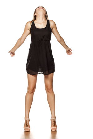 very happy young woman posing in short black dress