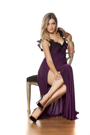bela jovem sentada na cadeira em um vestido longo com uma fenda profunda