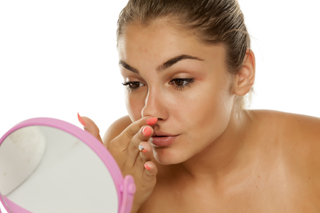 young girl touches her nose in the mirror