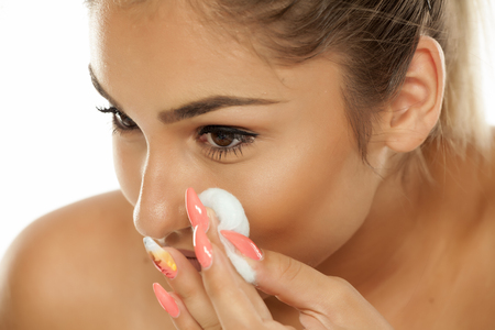 portrait of a young woman who cleans her face with cotton pads