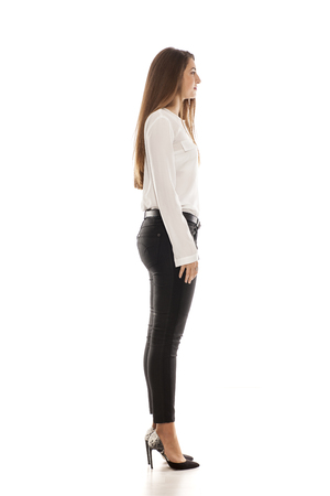 Side view of young woman in black jeans, white shirt and high heels