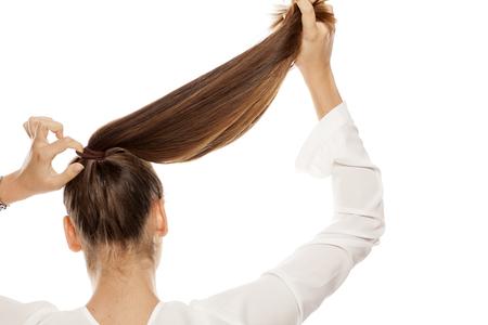Achteraanzicht van vrouwen die het haar in een paardenstaart strakker maakt