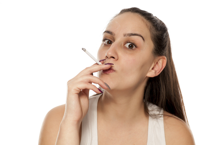A young, pretty woman smokes a cigar on a white background Stock fotó