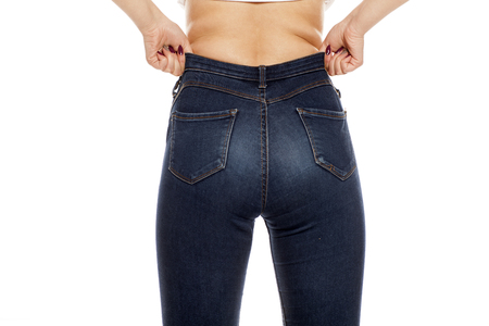 a young woman raising her jeans on white background