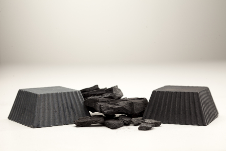 two hand made black soap from activated carbon on white background Stock Photo