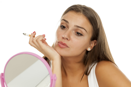young woman looking at herself in the mirror with a cigarette in her hand