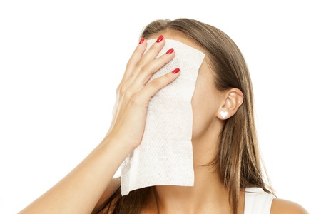 young beautiful woman removing makeup from her face