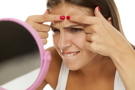 young woman looking at herself in the mirror and squeezing pimples Standard-Bild