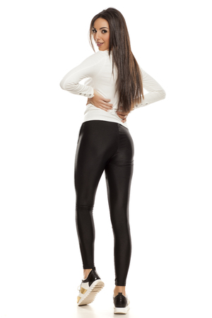 Back view of young beautiful woman in black tights, white blouse and sneakers on white background