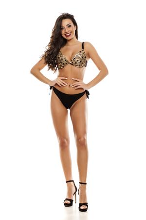 Beautiful fashion model in black bikini on white background