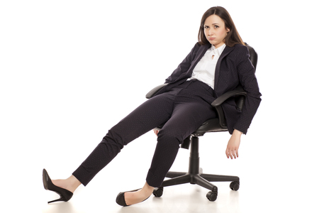tired businesswoman sitting in armchair on white background