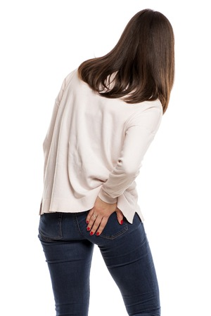 young woman with back pain on white background Stock Photo