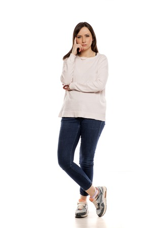 thoughtful and angry young woman on white background
