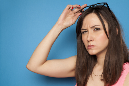 young woman looks suspiciously on a blue background Stock Photo