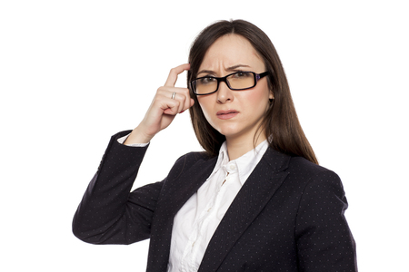 Confused businesswoman with questioning gesture posing on white background