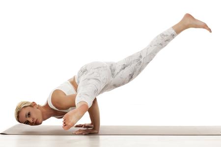 Split leg arm balance. Eka Pada Koundinyasana. Yoga, sport, training and lifestyle concept - Young blonde woman in white sportswear  doing yoga exercise.