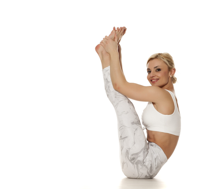 Yoga, sport, training and lifestyle concept - Young blonde woman in white sportswear doing yoga practice. Urdhva Mukha Paschimottanasana Stockfoto