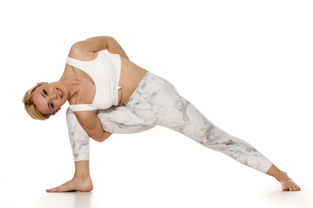 Yoga, sport, training and lifestyle concept - Young blonde woman in white sportswear doing yoga practice. Extended side angle pose, utthita parsvakonasana