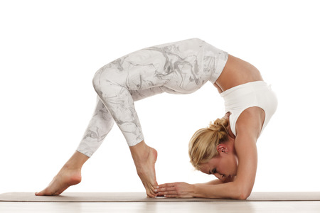 Yoga, sport, training and lifestyle concept - Young blonde woman doing yoga exercise. Portrait of young beautiful woman in white sportswear doing yoga practice.