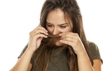 Nerveuze jonge vrouw die haar haar op witte achtergrond ruikt