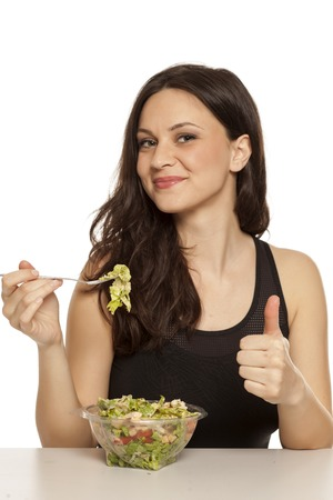 young beautiful woman eating a caaesar salad to go on white background