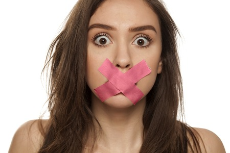 Young surprised woman with taped mouth on white background Zdjęcie Seryjne