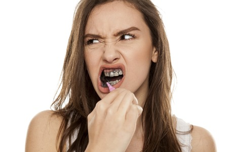 young woman brushing her teeth with a black tooth paste with active charcoal, and black tooth brush on white background 版權商用圖片 - 102311430