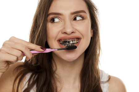 young woman brushing her teeth with a black tooth paste with active charcoal, and black tooth brush on white background, and showing thumbs up Stok Fotoğraf