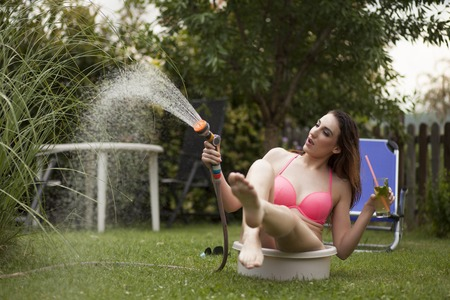 a young woman in a bikini having fun with a garden hose sitting in the washbowl