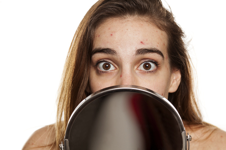 young unhappy woman with problematic skin and without makeup peeking behind the mirror on a white background