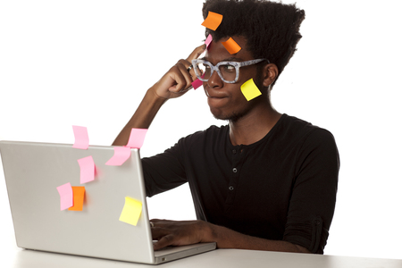 Confused young african man with stickers on his head and comuter on white background Stock Photo