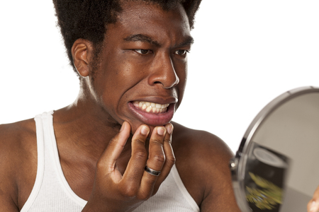 young handsome afro american guy checking his teeth in mirror on white background Standard-Bild