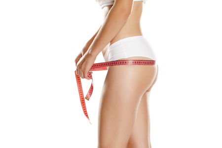 young slim woman measures her hips with measuring tape on white background