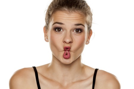 Portrait of beautiful young woman making fish face on white background