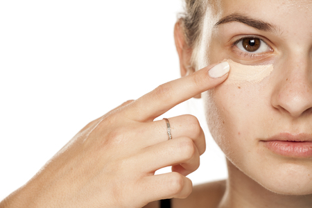 Young woman applying concealer under her eyes on white background Banco de Imagens
