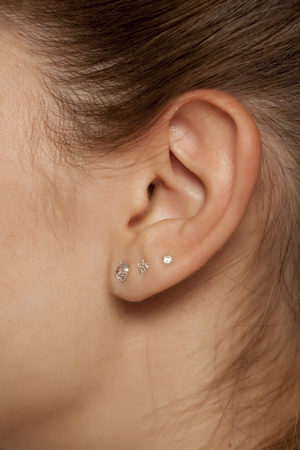 Closeup of female ear with three earrings Archivio Fotografico