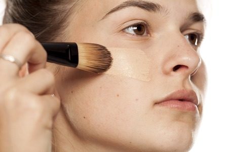 Young woman applying liquid foundation with brush on white background