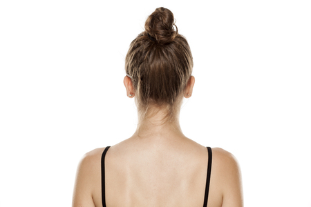 Rear view of young woman with bun on white background