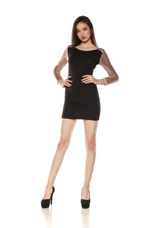 Young girl in a tight black dress on a white background