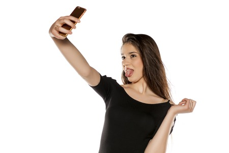 A young girl with long hair take selfies on a white background