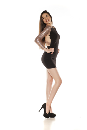 Young happy girl in a tight black dress on a white background 版權商用圖片