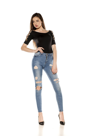 A young girl in a ripped jeans on white background