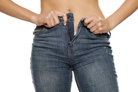 Junge Frau, die versucht, ihre Jeans auf weißem Hintergrund anzuziehen