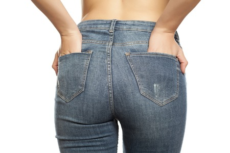 rear view of young woman posing in jeans on a white background Stock fotó