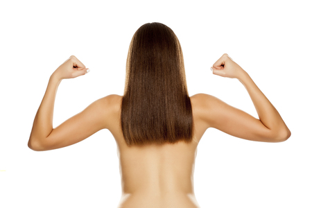 Back view of young nude woman with straight long hair, showing biceps on white background