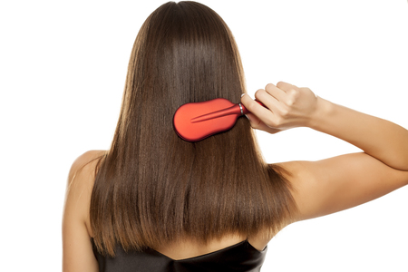 Back view of young woman combing her long hair on white background Foto de archivo