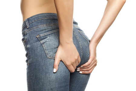 Young woman in jeans raises her buttocks on white background